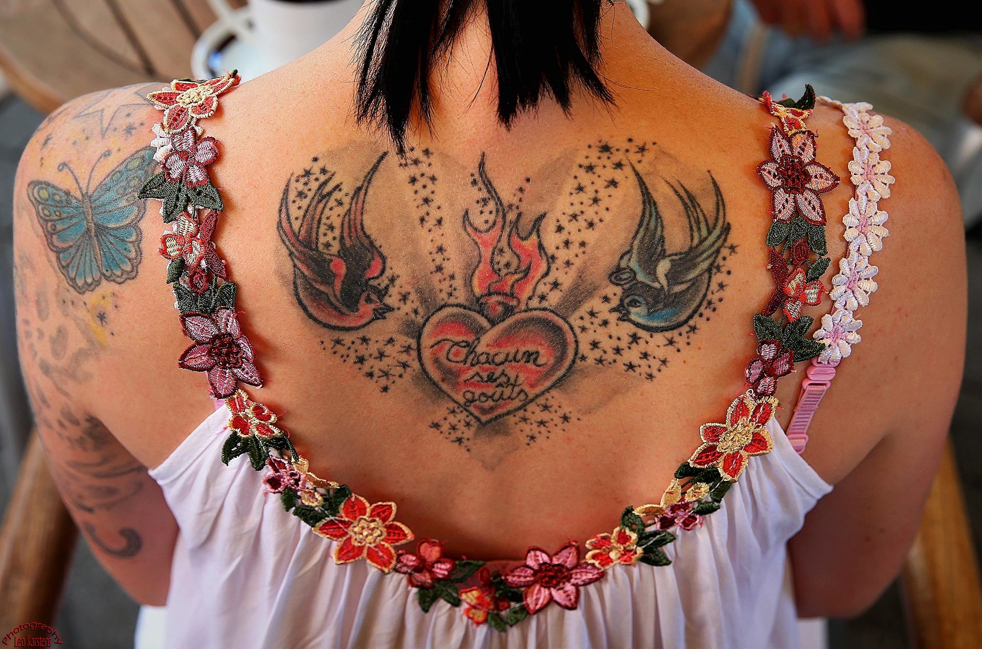 chica con un tatuaje en la espalda con corazón, pájaro y mariposa
