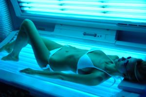 Mujer en una sesión de bronceado en un solárium horizontal