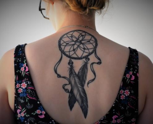 chica con tatuaje en la espalda en forma de atrapasueños