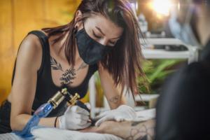 tatuadora con mascarilla haciendo un tatuaje en el antebrazo